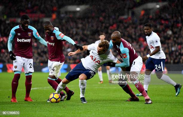 Harry Kane of Tottenham Hotspur is challenged by Pedro Obiang and Angelo Ogbonna of West Ham United during the Premier League match between Tottenham...