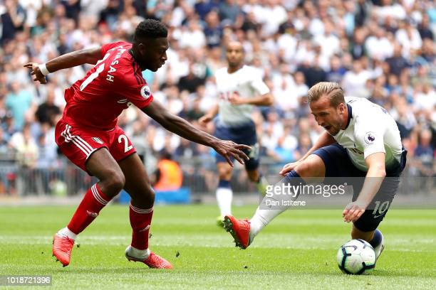 Harry Kane of Tottenham Hotspur is tackled by Timothy FosuMensah of Fulham during the Premier League match between Tottenham Hotspur and Fulham FC at...
