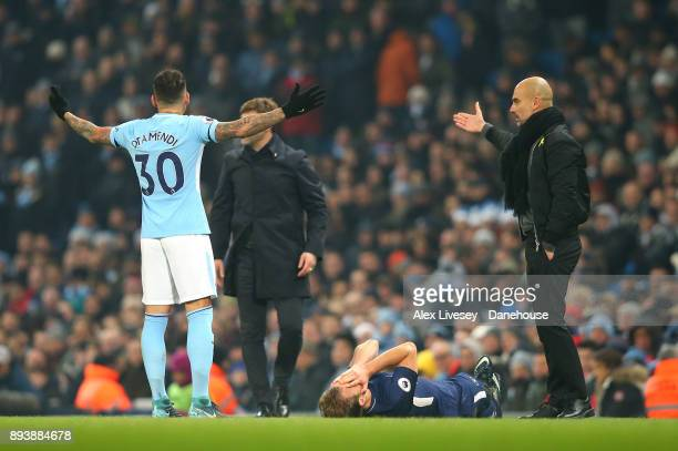 Harry Kane of Tottenham Hotspur lies injured as Nicolas Otamendi and Pep Guardiola of Manchester City protest during the Premier League match between...