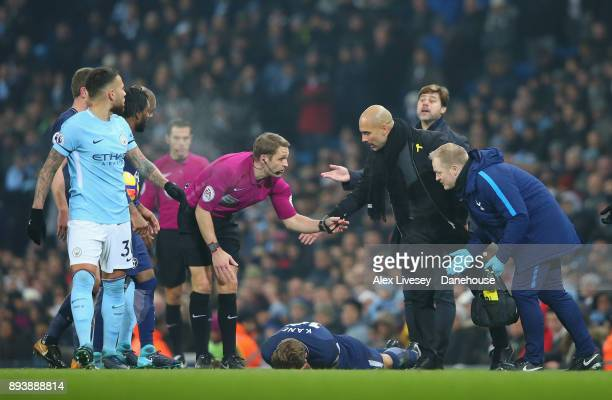 Harry Kane of Tottenham Hotspur lies injured as Nicolas Otamendi and Pep Guardiola of Manchester City protest to referee Craig Pawson during the...