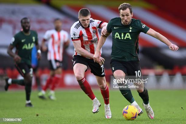 Harry Kane of Tottenham Hotspur looks to break past John Lundstram of Sheffield United during the Premier League match between Sheffield United and...