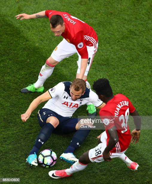 Harry Kane of Tottenham Hotspur Phil Jones of Manchester United and Axel Tuanzebe of Manchester United all battle for possesion during the Premier...