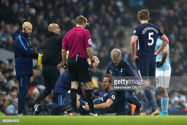 Harry Kane of Tottenham Hotspur receives treatment from the medical team during the Premier League match between Manchester City and Tottenham...