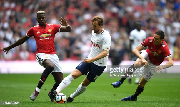 Harry Kane of Tottenham Hotspur runs with the ball away from Paul Pogba of Manchester United and Nemanja Matic of Manchester United during The...