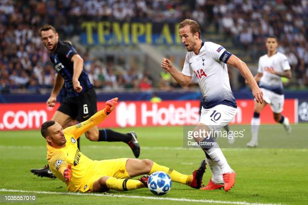 Harry Kane of Tottenham Hotspur runs with the ball under pressure from Samir Handanovic of Inter Milan during the Group B match of the UEFA Champions...