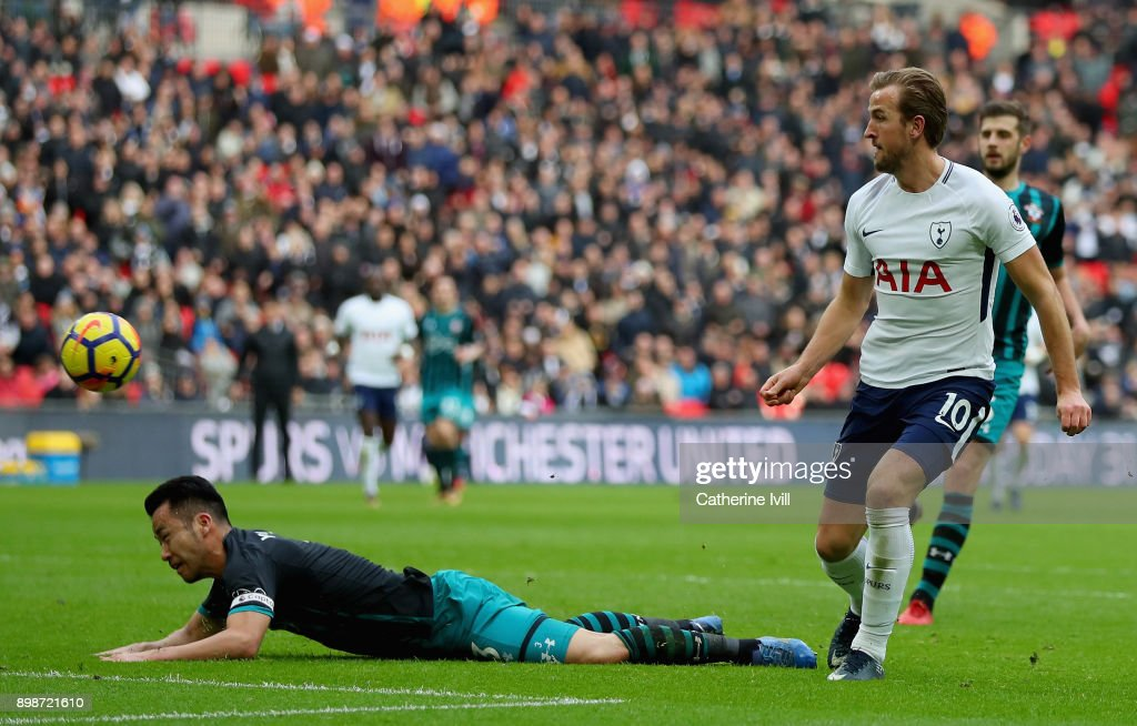 Harry Kane of Tottenham Hotspur scores his sides fifth goal as Maya Yoshida of Southampton attempts to tackle him during the Premier League match between Tottenham Hotspur and Southampton at Wembley Stadium on December 26, 2017 in London, England.