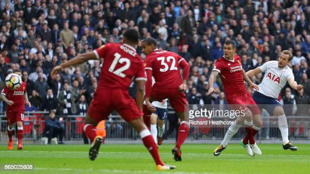 Harry Kane of Tottenham Hotspur scores his sides first goal while under pressure from Dejan Lovren of Liverpool during the Premier League match...
