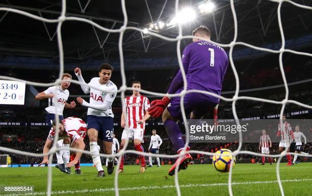 Harry Kane of Tottenham Hotspur scores his sides third goal past Jack Butland of Stoke City during the Premier League match between Tottenham Hotspur...