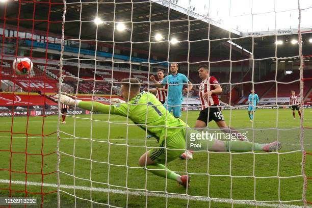 Harry Kane of Tottenham Hotspur scores his team's first goal past Dean Henderson of Sheffield United during the Premier League match between...