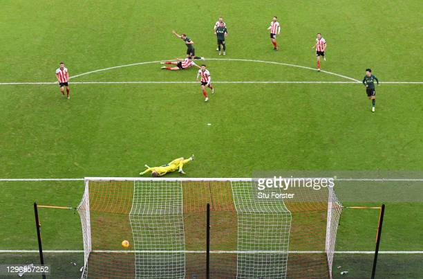 Harry Kane of Tottenham Hotspur scores their side's second goal past Aaron Ramsdale of Sheffield United during the Premier League match between...