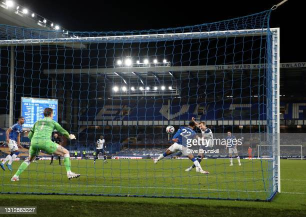Harry Kane of Tottenham Hotspur scores their team's second goal past Ben Godfrey of Everton during the Premier League match between Everton and...