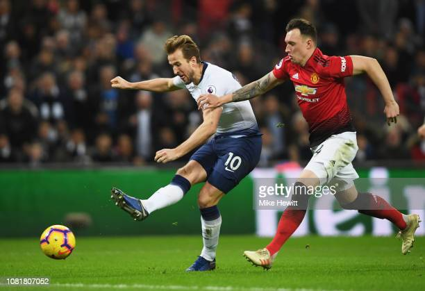 Harry Kane of Tottenham Hotspur shoots as he holds off Phil Jones of Manchester United during the Premier League match between Tottenham Hotspur and...