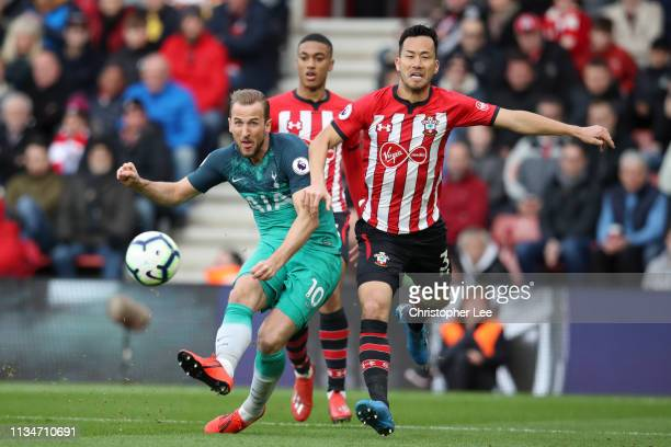 Harry Kane of Tottenham Hotspur shoots as he is challenged by Maya Yoshida of Southampton during the Premier League match between Southampton FC and...
