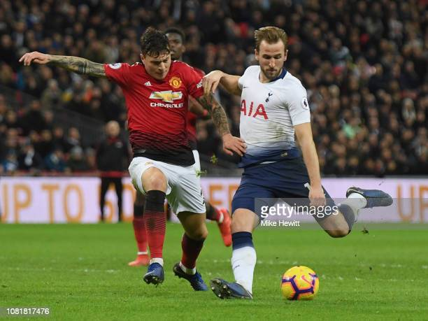 Harry Kane of Tottenham Hotspur shoots as Victor Lindelof of Manchester United challenges during the Premier League match between Tottenham Hotspur...