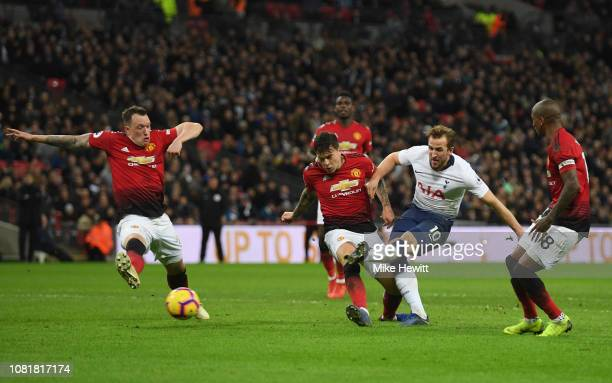 Harry Kane of Tottenham Hotspur shoots past Victor Lindelof and Phil Jones of Manchester United during the Premier League match between Tottenham...