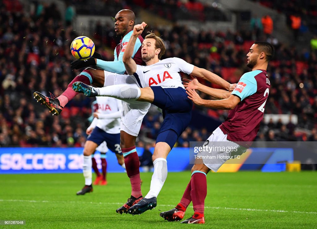 Harry Kane of Tottenham Hotspur shoots under pressure from Angelo Ogbonna and Winston Reid of West Ham United during the Premier League match between Tottenham Hotspur and West Ham United at Wembley Stadium on January 4, 2018 in London, England.