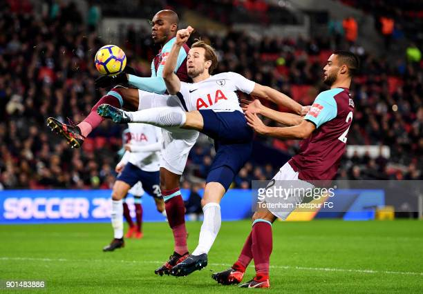 Harry Kane of Tottenham Hotspur shoots under pressure from Angelo Ogbonna and Winston Reid of West Ham United during the Premier League match between...