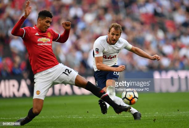 Harry Kane of Tottenham Hotspur shoots under pressure from Chris Smalling of Manchester United during The Emirates FA Cup Semi Final match between...