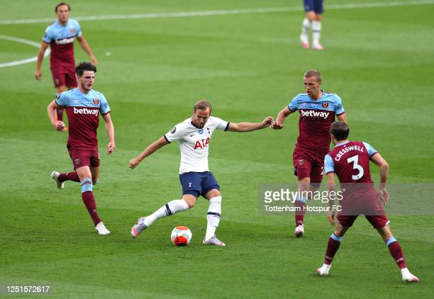 Harry Kane of Tottenham Hotspur shoots under pressure from Declan Rice Tomas Soucek and Aaron Cresswell of West Ham United during the Premier League...