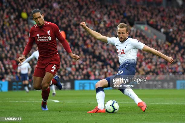 Harry Kane of Tottenham Hotspur shoots under pressure from Virgil Van Dijk of Liverpool during the Premier League match between Liverpool FC and...