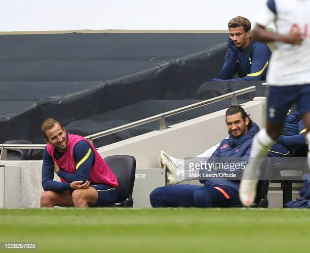 Harry Kane of Tottenham smiles on the substitute's bench with Dele Alli of Tottenham behind him looking not so happy during the Tottenham Hotspur v...