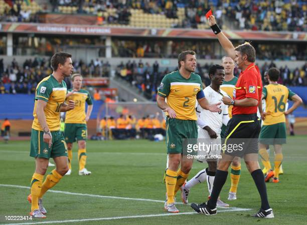 Harry Kewell and Lucas Neill of Australia argue with the referee Roberto Rosetti as he sends off Kewell for handball and awards Ghana a penalty...