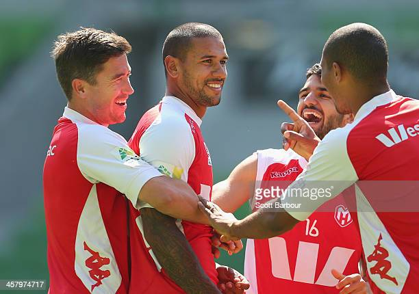 Harry Kewell holds Patrick Gerhardt as Aziz Behich of the Heart looks on during a Melbourne Heart ALeague training session at AAMI Park on December...