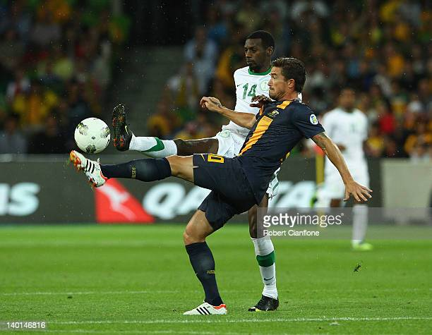 Harry Kewell of Australia is challenged by Saud Ali Khariri of Saudi Arabia during the Group D 2014 FIFA World Cup Asian Qualifier match between...