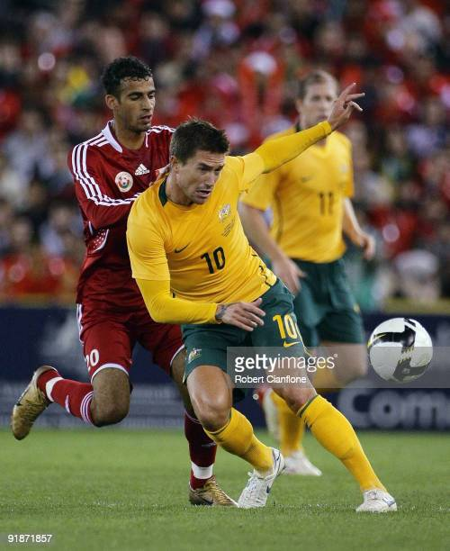 Harry Kewell of Australia is challenged during the Asian Cup Group B qualifying match between the Australian Socceroos and Oman at Etihad Stadium on...