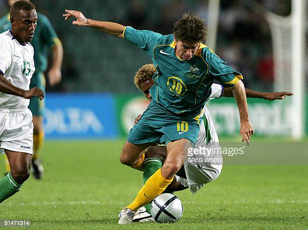 Harry Kewell of Australia is tackled from behind by Sale Kalifa of the Solomon Islands as George Lui moves in during the second leg of the Oceania...