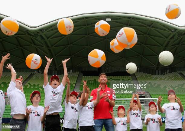 Harry Kewell of the Melbourne Heart football team looks on as children throw balls in the air during the launch of 'Premier's Active April' at AAMI...