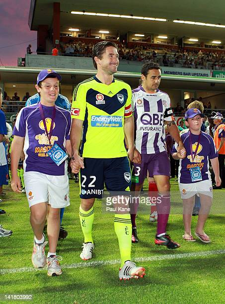Harry Kewell of the Victory and Travis Dodd of the Glory walk out onto the pitch with junior mascots during the round 25 ALeague match between the...