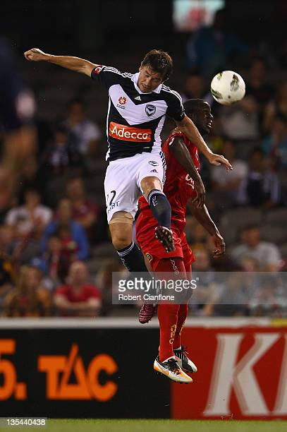 Harry Kewell of the Victory heads the ball in front of Bruce Djite of United during the round 10 ALeague match between the Melbourne Victory and...