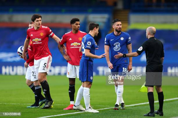 Harry Maguire and Marcus Rashford of Manchester United and Cesar Azpilicueta and Olivier Giroud of Chelsea interact with Simon Long, Assistant...