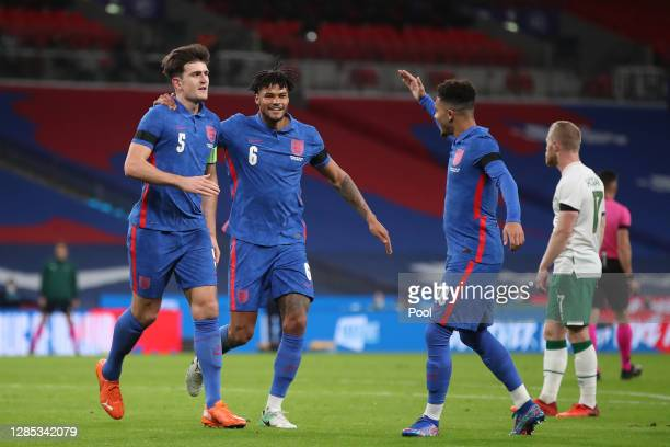 Harry Maguire of England celebrates with Tyrone Mings and Jadon Sancho of England after he scores his sides first goal during the international...