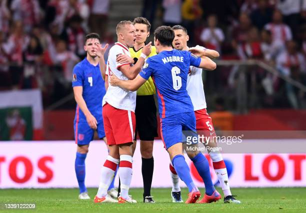 Harry Maguire of England clashes with Kamil Glik and Jan Bednarek of Poland during the 2022 FIFA World Cup Qualifier match between Poland and England...