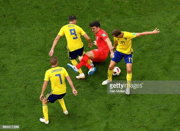 Harry Maguire of England is tackled by Marcus Berg and Viktor Claesson of Sweden of Sweden during the 2018 FIFA World Cup Russia Quarter Final match...