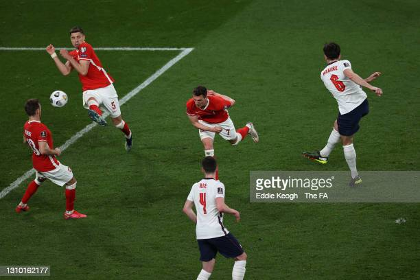 Harry Maguire of England scores their side's second goal whilst under pressure from Arkadiusz Milik of Poland during the FIFA World Cup 2022 Qatar...
