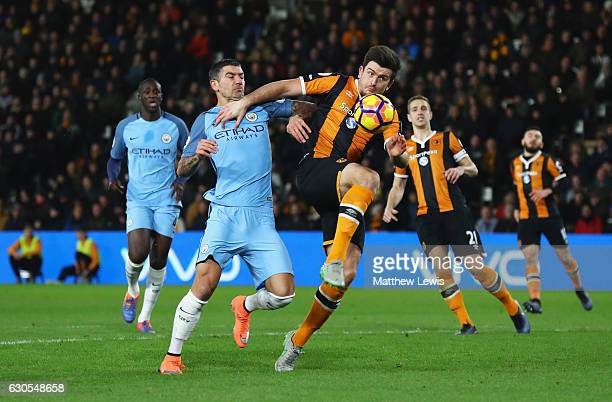 Harry Maguire of Hull City holds off Aleksandar Kolorov of Manchester City during the Premier League match between Hull City and Manchester City at...
