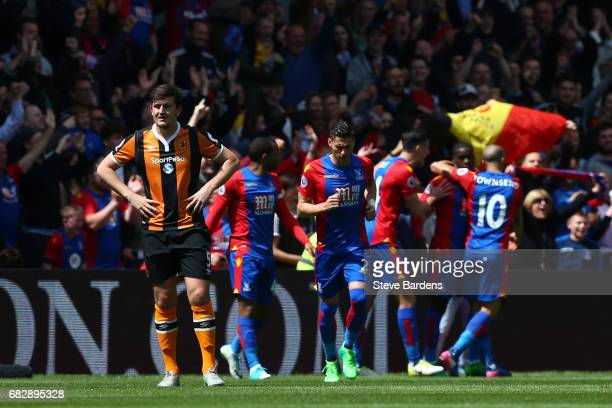 Harry Maguire of Hull City looks dejected as Crystal Palace players celebrate their first goal during the Premier League match between Crystal Palace...
