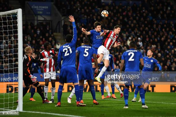 Harry Maguire of Leicester and Chris Basham of Sheffield battle in the air during The Emirates FA Cup Fifth Round match between Leicester City and...