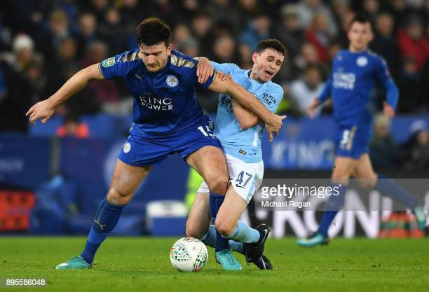 Harry Maguire of Leicester City holds off Phil Foden of Manchester City during the Carabao Cup QuarterFinal match between Leicester City and...