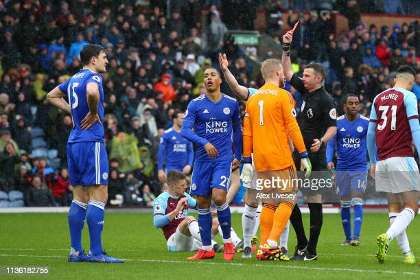 Harry Maguire of Leicester City is shown a red card by referee Michael Oliver during the Premier League match between Burnley FC and Leicester City...