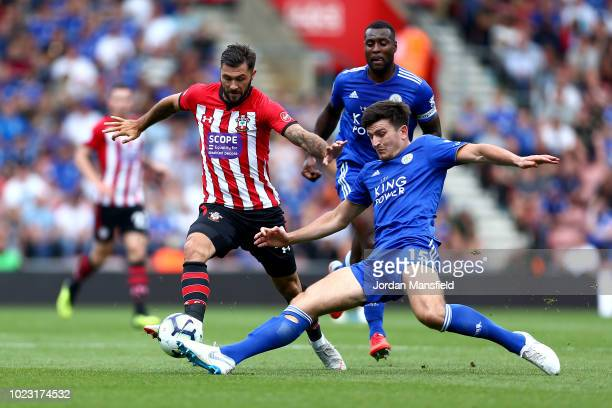 Harry Maguire of Leicester City tackles Charlie Austin of Southampton during the Premier League match between Southampton FC and Leicester City at St...
