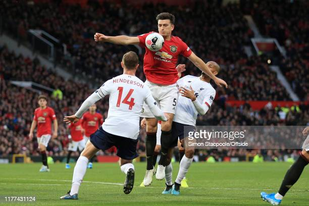 Harry Maguire of Man Utd in action with Fabinho of Liverpool and Jordan Henderson of Liverpool during the Premier League match between Manchester...