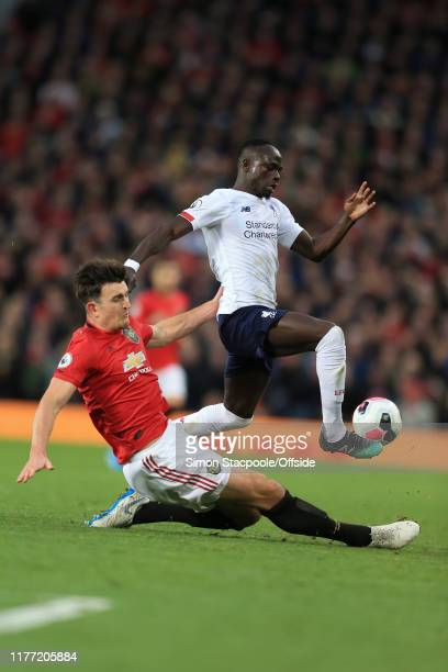 Harry Maguire of Man Utd tackles Sadio Mane of Liverpool during the Premier League match between Manchester United and Liverpool FC at Old Trafford...
