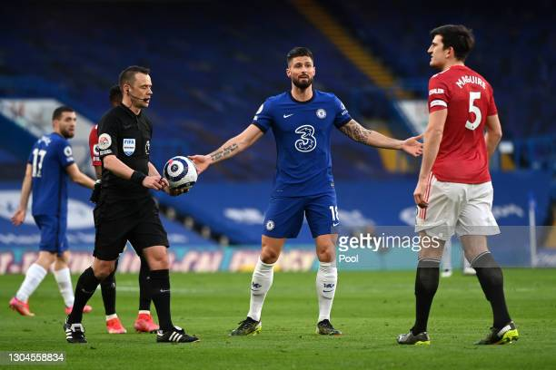 Harry Maguire of Manchester United and Olivier Giroud of Chelsea interact with Match Referee, Stuart Attwell after a VAR decision during the Premier...