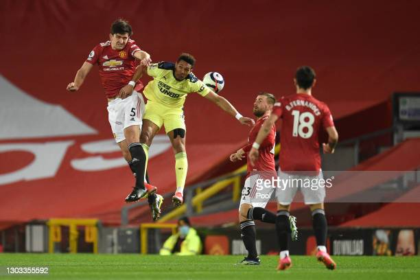 Harry Maguire of Manchester United battles for possession with Joelinton of Newcastle United during the Premier League match between Manchester...