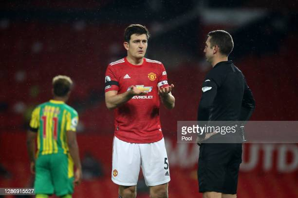 Harry Maguire of Manchester United confronts referee David Coote after he makes the decision to award West Bromwich Albion a penalty before a VAR...