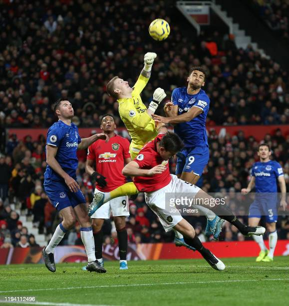 Harry Maguire of Manchester United in action with Jordan Pickford and Dominic Calvert-Lewin of Everton during the Premier League match between...